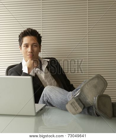 Businessman working on laptop with feet on desk