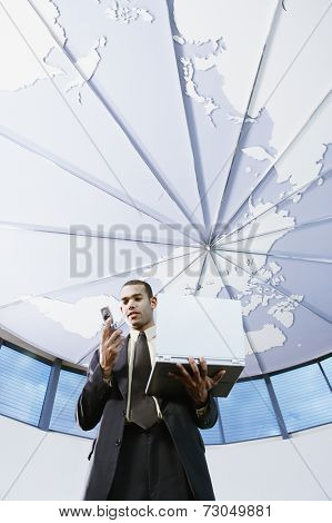 Low angle view of businessman with cell phone and laptop
