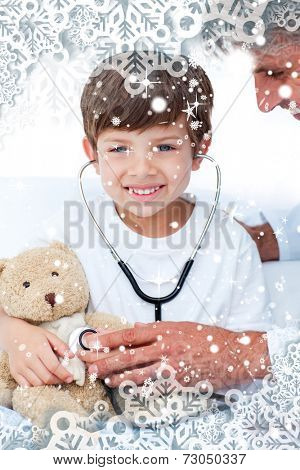 Adorable Little boy playing with his doctor against snow falling