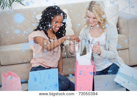 Two women look through shopping bags against snow falling