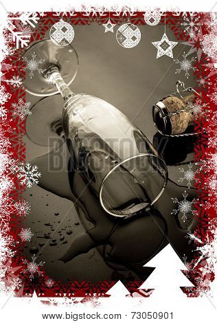 Christmas themed frame against knocked over champagne flute beside cork