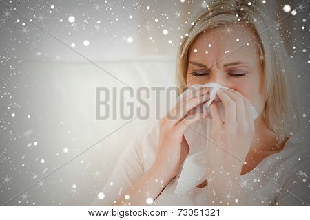 Composite image of ill woman blowing her nose against snow
