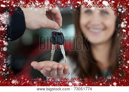 Composite image of woman smiling while receiving car keys against snow
