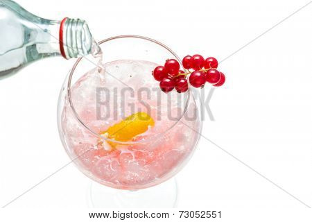 sparkly water being poured into Gin hard liquor drink with gooseberries fruits isolated on white