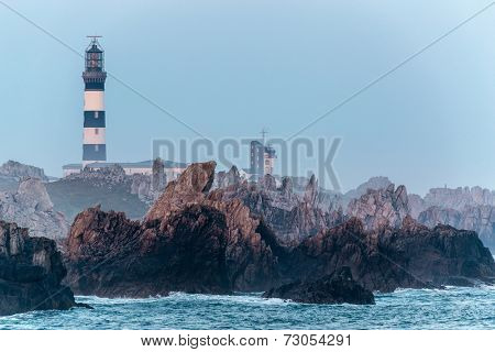 Sharp rocky coastline and Creach lighthouse in the Ushant island, Brittany, France