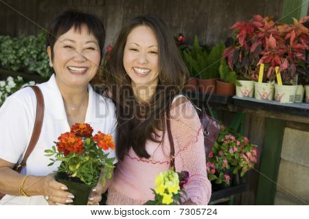 Woman With Mother Holding Flowers In Plant Nursery, Portrait