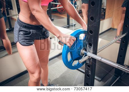 female hands on athletic barbell