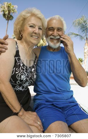 Senior Couple sitting outdoors man using mobile phone portrait.