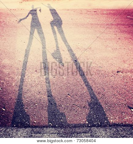 shadow of two people play fighting in the street toned with a retro vintage instagram filter (extremely grainy filter used)