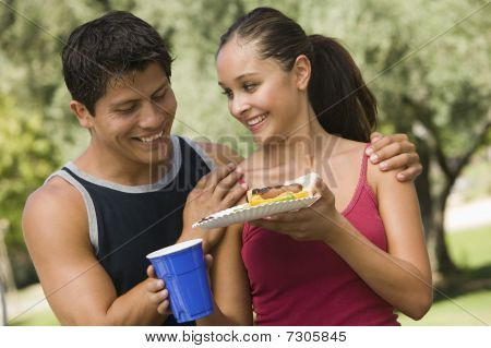 Young beautiful Mexican couple eating at a picnic.