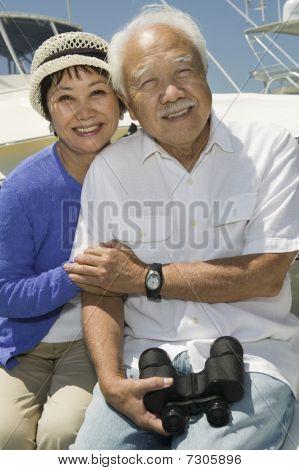 Senior couple with binoculars on boat (portrait)