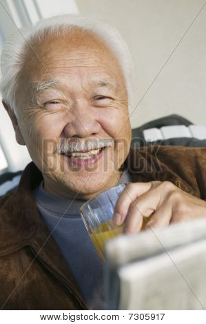Asian Man drinking orange juice and reading paper (portrait)