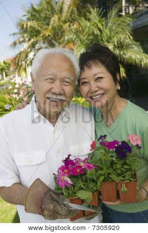 Asian Senior couple holding flowers outdoors (portrait)
