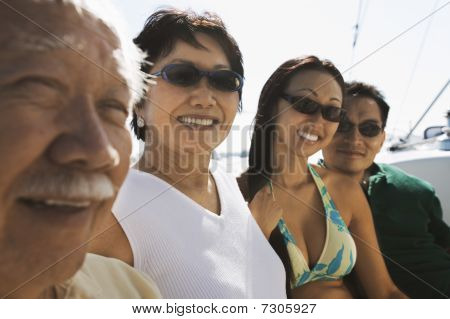 Asian family sitting on a boat in the ocean (portrait)