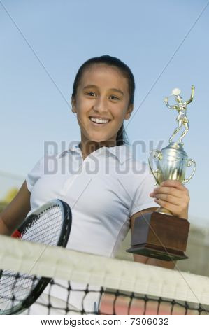 Young girl at net on tennis court holding trophy portrait low angle view