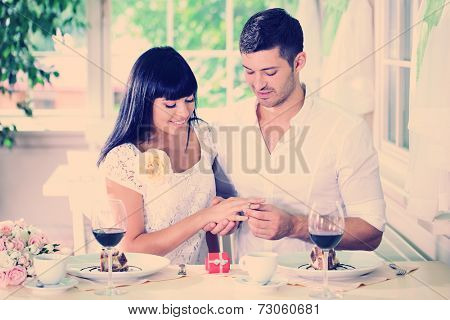 Man proposing and holding up an engagement ring his woman over restaurant table