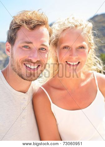 Young couple portrait. Beautiful young people smiling happy looking at camera in outdoors portrait. Candid real couple on sunny summer day. Woman and man in their 20s.