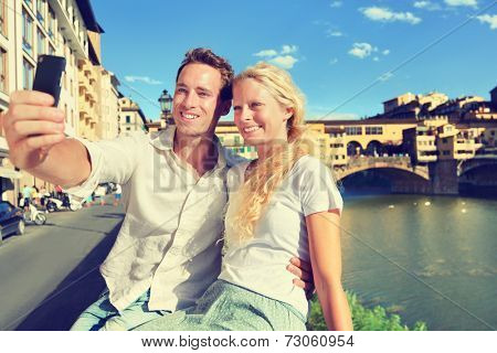 Selfie photo by couple traveling in Florence. Romantic travel woman and man in love smiling happy taking self portrait outdoor by Ponte Vecchio during vacation holidays in Tuscany, Italy, Europe