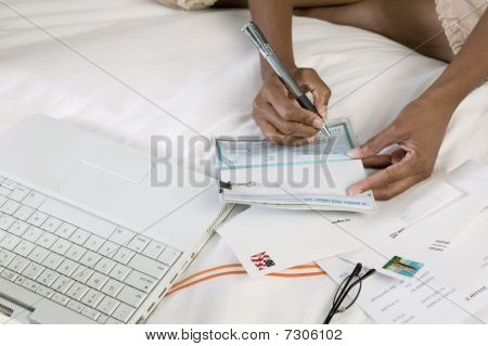 Woman Writing cheque on bed by laptop close up of hands high angle view