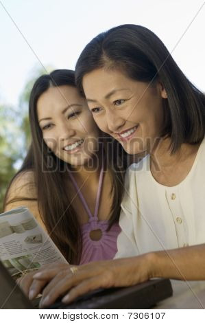 Mother and Daughter sitting at backyard table Using Laptop Together