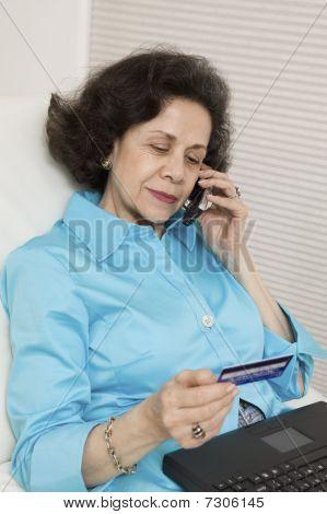 Mulher usando cartão de crédito e telefone celular para fazer a compra on-line