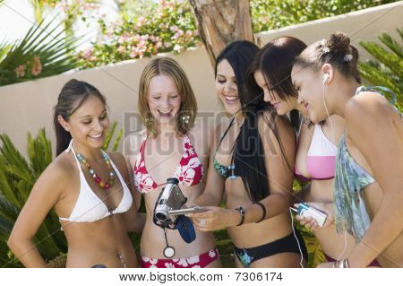 Young women in swimsuits in backyard looking at video camera screen