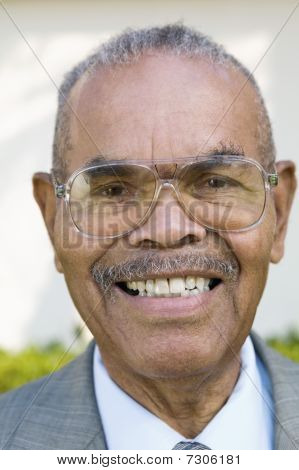 Senior Man wearing glasses and smiling portrait close up
