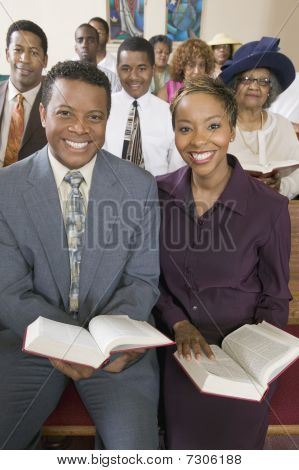 Young couple with Bibles sitting on church pews portrait