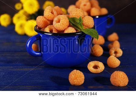 Yellow raspberries in dark blue mugs and wildflowers on wooden table on dark background