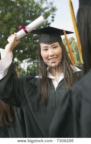 Young female ethnic Graduate hoisting Diploma into air