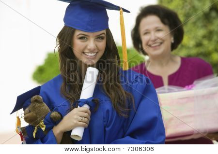 Graduate holding teddy bear and diploma outside portrait