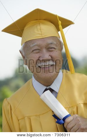 Senior Graduate holding diploma outside front view portrait