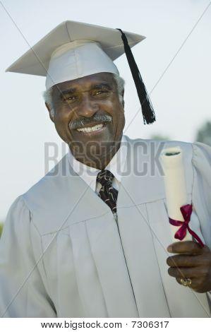 Senior Graduate (Smiling) holding diploma outside portrait