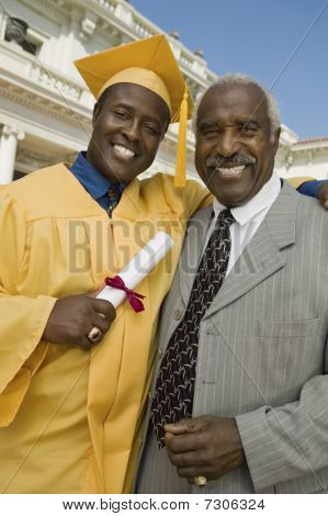 Ethnic Graduate with father outside university portrait