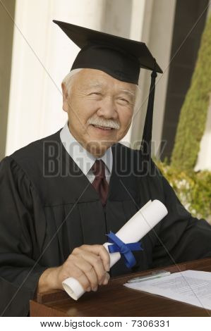 Senior graduate with diploma at podium outside portrait