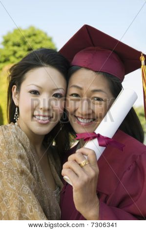Ethnic Senior Graduate hugging daughter outside portrait