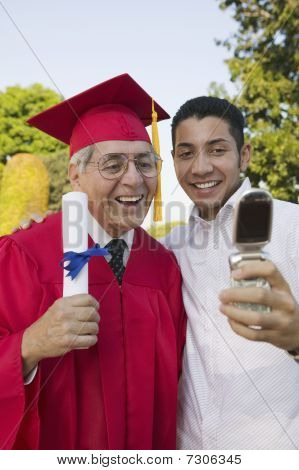 Senior Graduate and son taking picture with cell phone outside