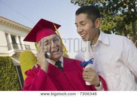 Senior Graduate using cell phone outside with son low angle view