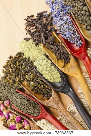 assortment of dry tea leaves and addition in spoon scoops close up  on wooden table background