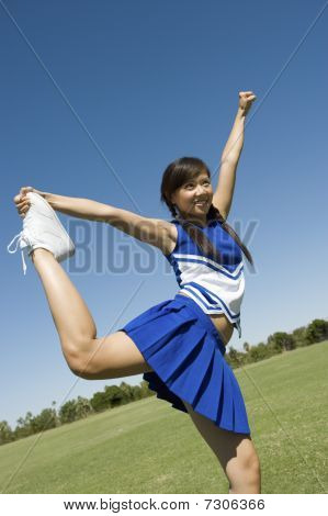 Teenage Cheerleader stretching on lawn low angle portrait