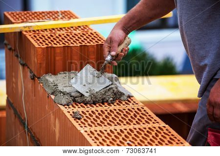 anonymous construction worker on a building site when building a house built a wall of brick. brick wall of a solid house. symbolic image for illegal work and bungling