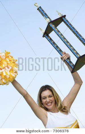 Sorrindo Cheerleader segurando o troféu (retrato) (vista de ângulo baixo)