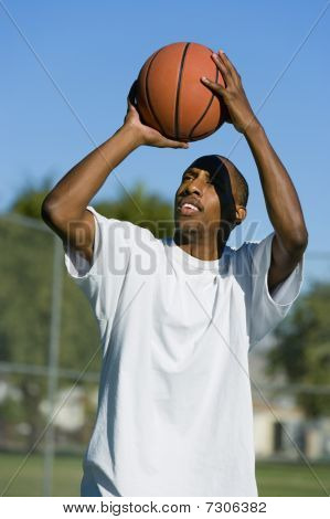 Ethnic Man aiming to shoot basketball (portrait)