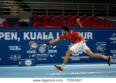 SEPTEMBER 23, 2014 - KUALA LUMPUR, MALAYSIA: Philipp Oswald from Austria chases to return a shot in his first round match at the Malaysian Open Tennis 2014 event. This is an ATP sanctioned tournament.
