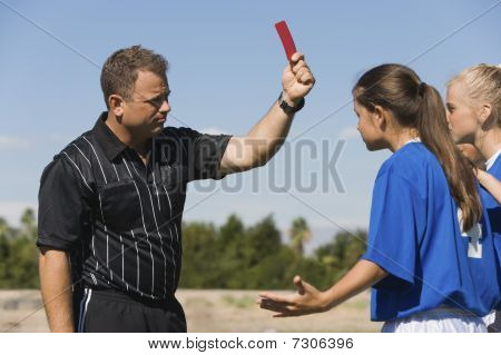Referee showing red card to girls (13-17) playing soccer