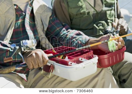 Two men using tackle box and preparing fishing pole (close-up) (mid section)