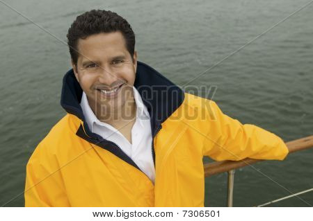 Man wearing yellow anoraks on yacht (portrait) (elevated view)