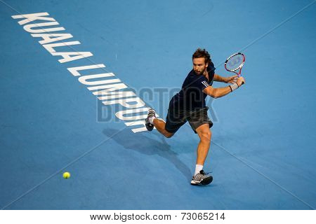 SEPTEMBER 25, 2014 - KUALA LUMPUR, MALAYSIA: Ernests Gulbis of Latvia chases to make a backhand return in his match at the Malaysian Open Tennis 2014. This is an ATP sanctioned tournament.