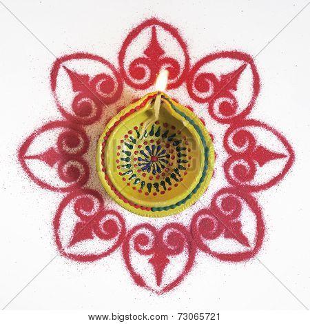 A Diwali-lamp placed on a Rangoli pattern - bird eye view