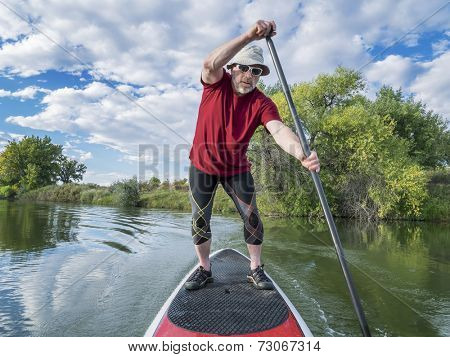 senior male paddler enjoying workout on stand up paddleboard (SUP), calm lake in Colorado, late summer